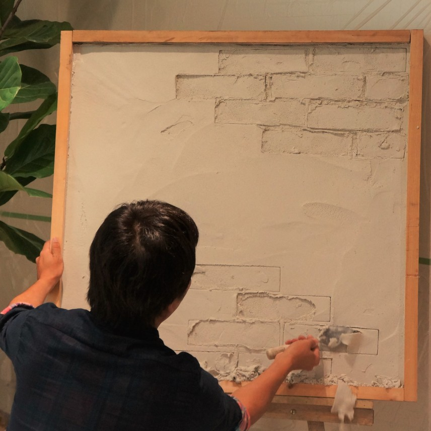 まだ柔らかい塗り壁にレンガの型をつけ、立体感をだしていく